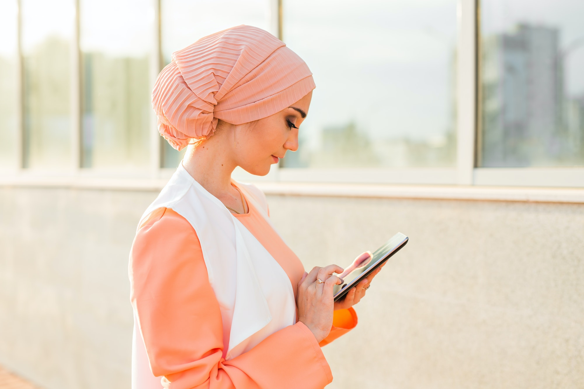 Portrait of Arab businesswoman holding a tablet. The woman is dressed in an abaya